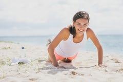 Lyckligt sunt göra för kvinna skjuter upp på stranden royaltyfria bilder