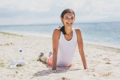 Lyckligt sunt göra för kvinna skjuter upp på stranden arkivfoton