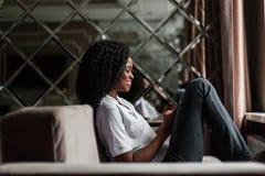 Lyckligt svart kvinnasammanträde på soffan och innehavet en telefon Kvinna som skriver en messege Arkivbilder