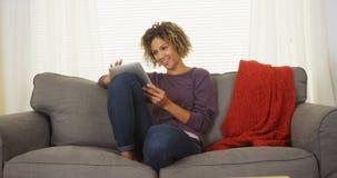 Lyckligt svart kvinnasammanträde på soffan genom att använda minnestavlan Royaltyfri Foto