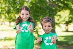 Lyckligt syskon i gräsplan med tummar upp arkivfoton