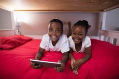 Lyckligt syskon med den digitala minnestavlan som hemma ligger på säng Royaltyfria Bilder