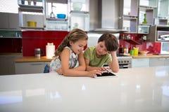 Lyckligt syskon som använder den digitala minnestavlan i kök Royaltyfri Fotografi