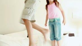 Lyckligt syskon som hoppar på en madrass lager videofilmer