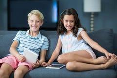Lyckligt syskon som sitter på soffan med den digitala minnestavlan i vardagsrum Royaltyfri Bild