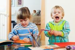 Lyckligt syskon som spelar med blyertspennor Royaltyfri Foto