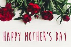 Lyckligt tecken för text för dag för moder` s på härliga röda pioner på vit w Royaltyfri Foto