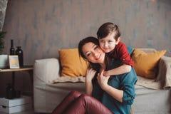 lyckligt tillsammans hemmastatt för moder och för son och att sitta på den hemtrevliga soffan royaltyfri foto