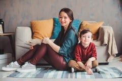 lyckligt tillsammans hemmastatt för moder och för son och att sitta på den hemtrevliga soffan arkivbilder