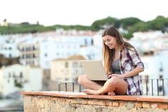 Lyckligt tonårigt genom att använda en bärbar dator som sitter på en avsats på en stad royaltyfri bild