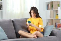Lyckligt tonårigt i gul användande telefon hemma royaltyfri bild