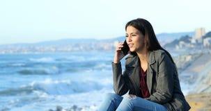 Lyckligt tonårigt samtal på telefonen på stranden stock video