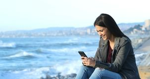 Lyckligt tonårigt smsa på telefonen på stranden