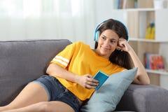 Lyckligt tonårigt tyckande om lyssna till musik på en soffa hemma royaltyfri fotografi