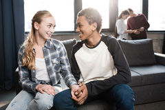 Lyckligt tonårs- parsammanträde på soffa- och innehavhänder med vänner som bakom står Arkivfoton
