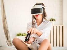 Lyckligt tycka om för kvinna som spelar VR-virtuell verklighethörlurar med mikrofon Royaltyfri Foto