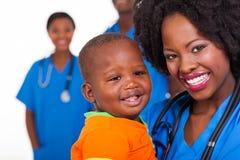 Den afrikanska sjuksköterskan behandla som ett barn Royaltyfri Foto