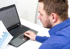 Lyckligt ungt arbete för affärsman i modernt kontor på datoren Royaltyfri Bild