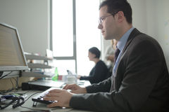 Lyckligt ungt arbete för affärsman i modernt kontor Stilig affärsman In Office Verkliga ekonombussinesmen, inte en modell arkivbilder