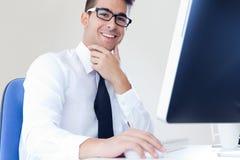 Lyckligt ungt arbete för affärsman i modernt kontor på datoren Arkivbilder
