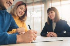 Lyckligt ungt asiatiskt par- och fastighetsmäklaremedel Gladlynt ung man som undertecknar något dokument, medan sitta på skrivbor arkivfoto
