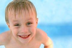 Lyckligt ungt barn som ler i simbassäng royaltyfria foton