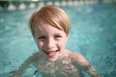Lyckligt ungt barn som skrattar i simbassäng arkivfoto
