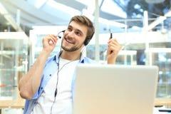 Lyckligt ungt manligt ut?vande arbete f?r kundservice i regeringsst?llning royaltyfri foto