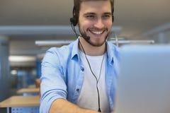 Lyckligt ungt manligt ut?vande arbete f?r kundservice i regeringsst?llning arkivfoto