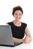 Lyckligt ungt sammanträde för affärskvinna på skrivbordet med bärbara datorn royaltyfri bild
