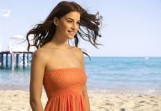 Lyckligt ungt tillfälligt kvinnaanseende på stranden Royaltyfri Fotografi