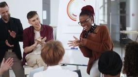 Lyckligt upphetsat ungt afrikanskt kvinnligt framstickande som skrattar och applåderar som ger presentationssamtal till kollegor  lager videofilmer