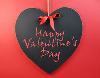 Lyckligt valentin dagmeddelande som är skriftligt på hjärtablackboarden. Arkivbild
