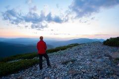 Lycksökare som beundrar panoraman av bergen under solnedgång Royaltyfri Fotografi