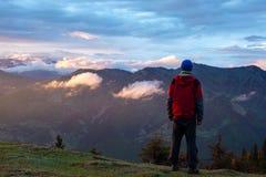 Lycksökaren beundrar solnedgång i bergen efter storm Royaltyfri Fotografi