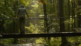 Lycksökaren går över bron i skogen arkivfilmer