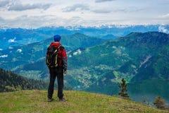 Lycksökaren med ryggsäcken står på den gröna bergängen Arkivbild