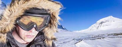 Lycksökaren/skidåkaren/snowboarderen med skidar skyddsglasögon och en pälshuv royaltyfri foto