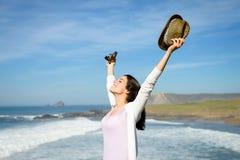 Lycksalig kvinna som lyfter armar in mot havet Royaltyfri Fotografi
