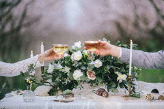 Lyfta exponeringsglas med champagne på brölloptabellen royaltyfri bild