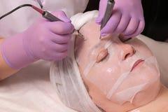 Lyfta för hud Microcurrent släta av skrynklor En yrkesmässig cosmetologist i lila handskearbeten med två elektroder till och med  royaltyfri bild