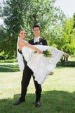Lyftande brud för lycklig brudgum i armar på trädgården Royaltyfria Bilder