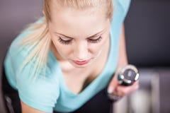 Lyftande hantel för attraktiv blond sportflicka Fotografering för Bildbyråer