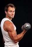 Lyftande hantel för muskulös man Arkivbild