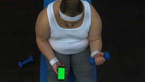 Lyftande hantel för sjukligt fet man och hållande ögonen på video smartphone för kondition, grön skärm lager videofilmer