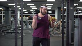 Lyftande hantel för sjukligt fet man och hållande hamburgare i handen, livbeslut, motivation stock video