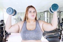 Lyftande hantlar för sjukligt fet kvinna på idrottshallen Arkivbild