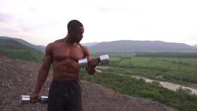 Lyftande hantlar för stilig svart man för afrikansk amerikan muskulös mot bakgrunden för molnig himmel stock video