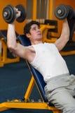 Lyftande hantlar för ung man i sportklubba Royaltyfria Bilder