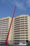 Lyftande hydraulisk kran på konstruktion av flervånings- byggnad Arkivbilder